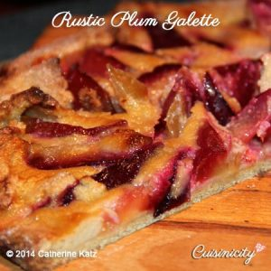 Lateral view of a half a Rustic Plum Galette on a brown wooden cutting board