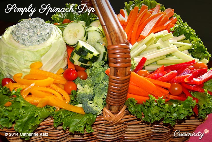 Simply Spinach Dip heaped into a hollowed out cabbage with veggies in a brown wicker basket