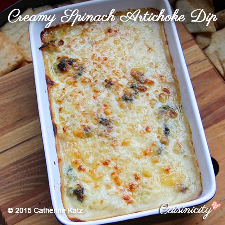 Bubbling Creamy Spinach Artichoke Dip in a small white baking pan