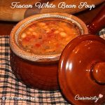 Tuscan White Bean Soup fills a brown ceramic bowl with bowl top leaning on right side