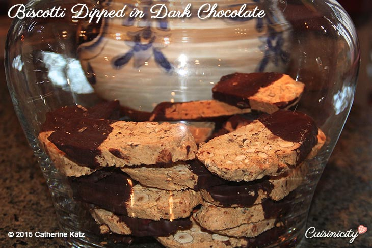 Several brown Biscotti Dipped in Dark Chocolate made with hazelnuts and almonds in a large, tall glass cookie jar