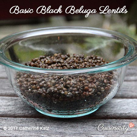 Glass bowl filled with a generous helping of Basic Black Beluga Lentils outside on a picnic table.