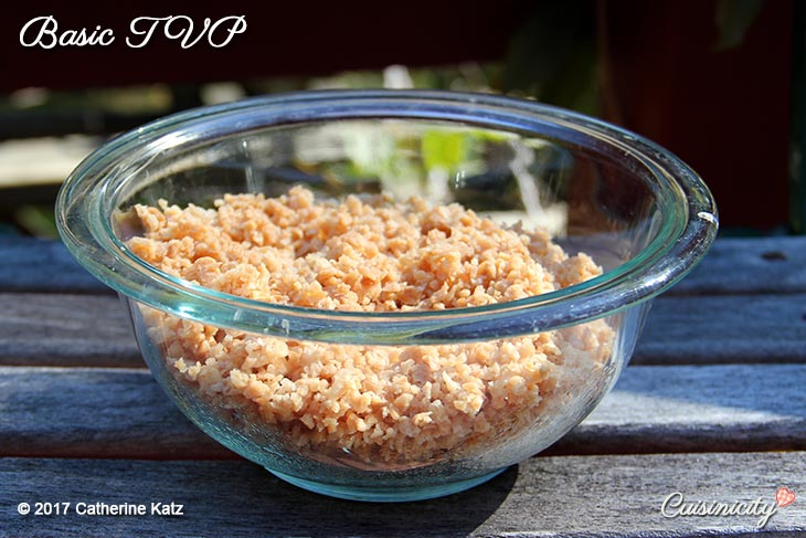 A glass bowl of Basic Textured Vegetable Protein (TVP) outside on a gray picnic table on a nice sunny day