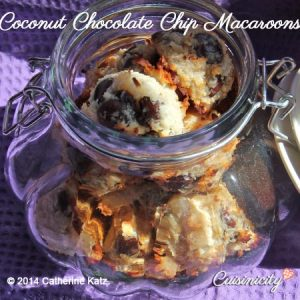 Coconut Chocolate Chip Macaroons in an ornate glass cookie jar on a deep purple placemat