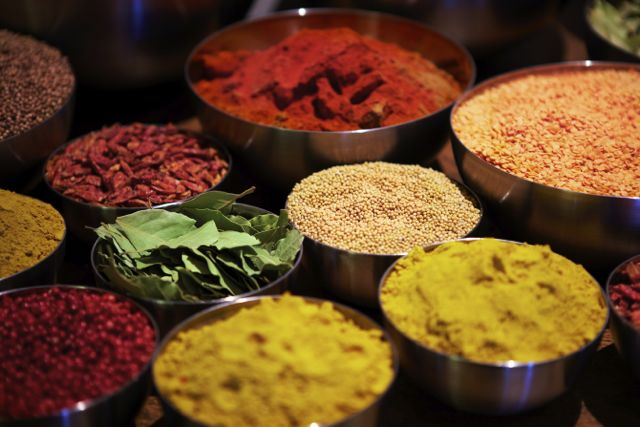 Some metal bowl filled with an assortment of different coloured spices