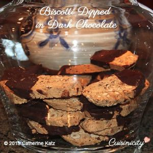 Biscotti with hazelnuts and almonds Dipped halfway in Dark Chocolate in a glass cookie jar