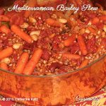 A glass bowl filled with the red, oranges and browns of Mediterranean Barley Stew