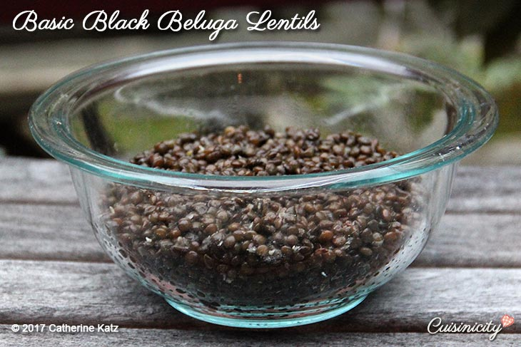 Delicious heaping helping of Basic Black Beluga Lentils outside on a picnic table in a glass bowl