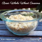 A glass bowl filled with Basic Whole Wheat Couscous sits outside on a gray table.