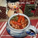 Bean Pot au Feu in a blue-gray ceramic bowl sits on a red-with-white-striped cloth placemat and decorative snowman in the background.