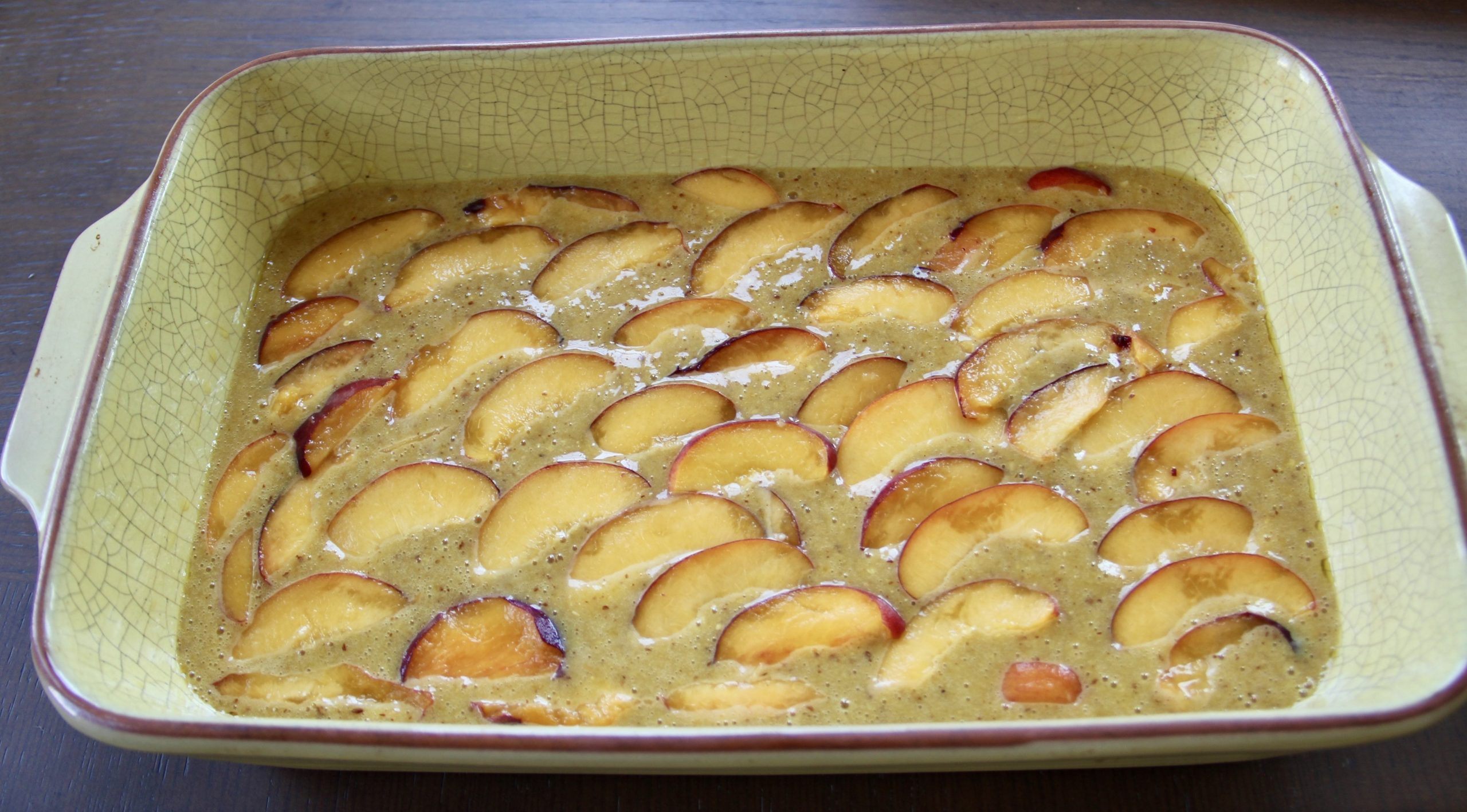 Sliced peaches on top of raw batter before it goes into the oven