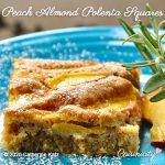 A generous Peach Almond Polenta Squares slice on a blue plate snuggles next to two peach slices and a rosemary garnish.