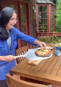 Chef Catherine Katz places basil on the finished pizza outside on her deck by the wooden picnic table